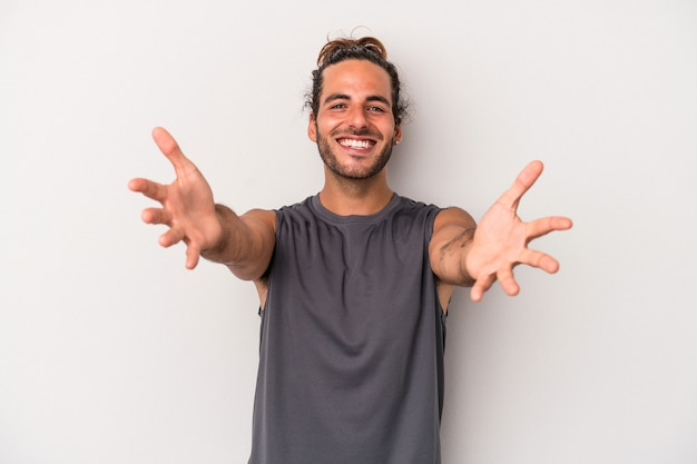 Young caucasian man isolated on gray background feels confident giving a hug to the camera.
