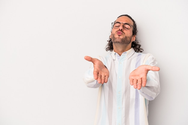 Young caucasian man isolated on gray background folding lips and holding palms to send air kiss.