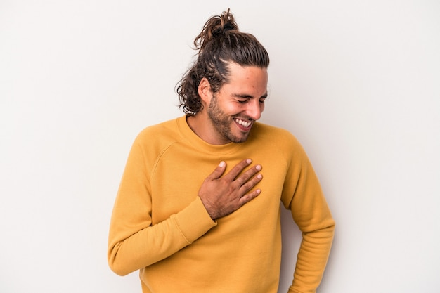 Young caucasian man isolated on gray background laughing keeping hands on heart, concept of happiness.