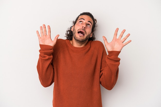 Young caucasian man isolated on gray background screaming to the sky, looking up, frustrated.