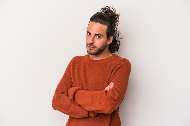 Young caucasian man isolated on gray background suspicious, uncertain, examining you.