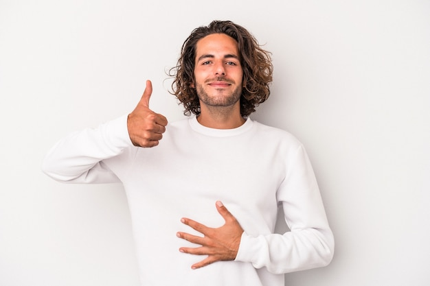 Young caucasian man isolated on gray background touches tummy, smiles gently, eating and satisfaction concept.