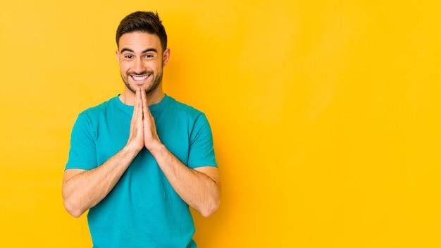 自信を持って若い白人男性は口の近くの祈りで手をつないで分離されたと感じています。