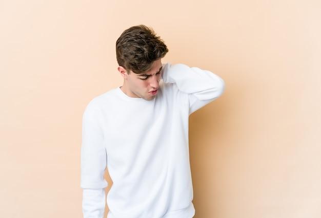 ストレス、マッサージ、手で触れることによる首の痛みを持つベージュの壁に分離された若い白人男性。
