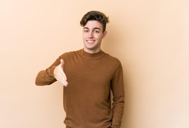 Молодой кавказский человек, изолированные на бежевой стене, протягивая руку на камеру в жесте приветствия.