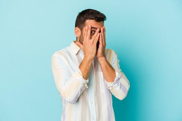 Молодой кавказский человек, изолированные на синем фоне, мигает сквозь пальцы испуганно и нервно.