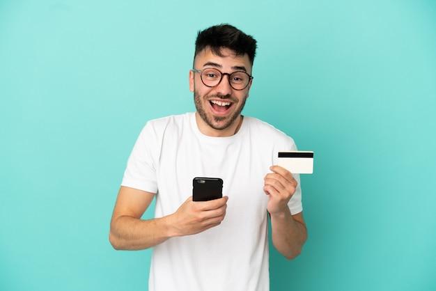 파란 배경에 격리된 백인 청년은 휴대폰으로 구매하고 놀란 표정으로 신용카드를 들고 있다