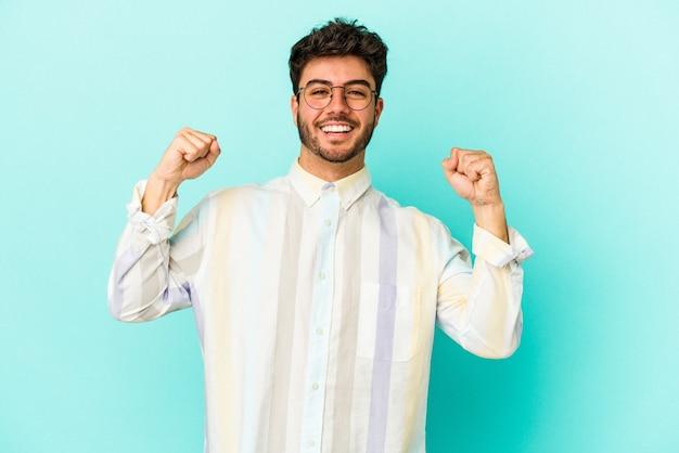 勝利、情熱、熱意、幸せな表情を祝う青の背景に若い白人男性。