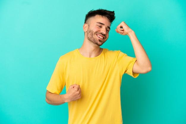 Молодой кавказский человек, изолированные на синем фоне, празднует победу