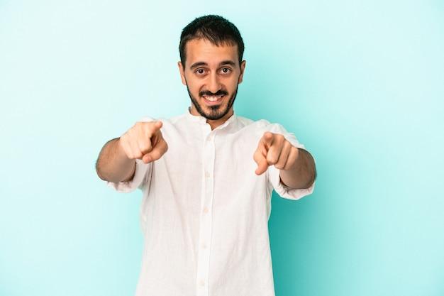 青の背景に孤立した若い白人男性は、正面を指している陽気な笑顔。