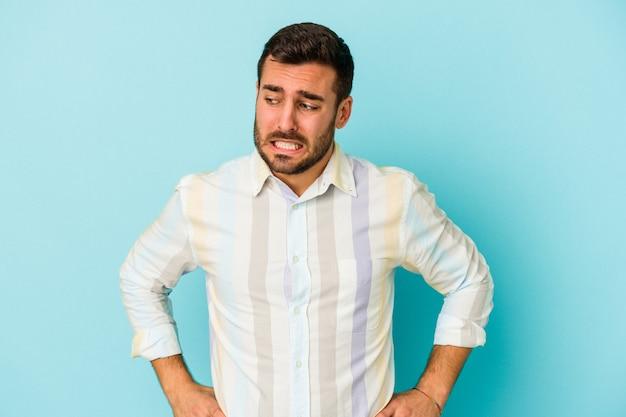 Молодой кавказский человек, изолированные на синем фоне, смущен, чувствует себя сомнительным и неуверенным.