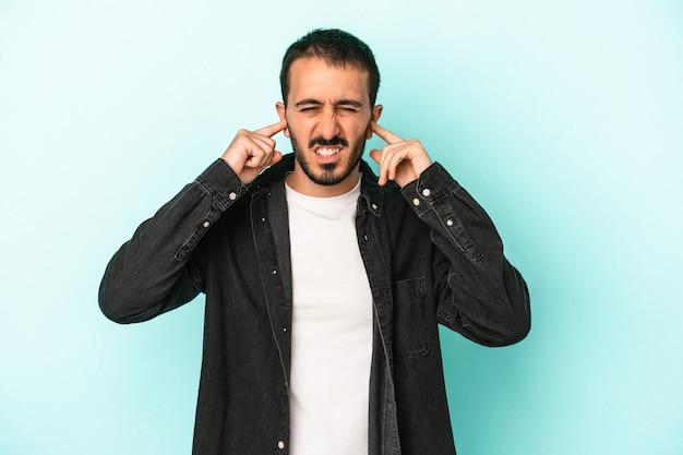 指で耳を覆っている青い背景に孤立した若い白人男性は、大声で周囲にストレスを感じ、必死になっています。