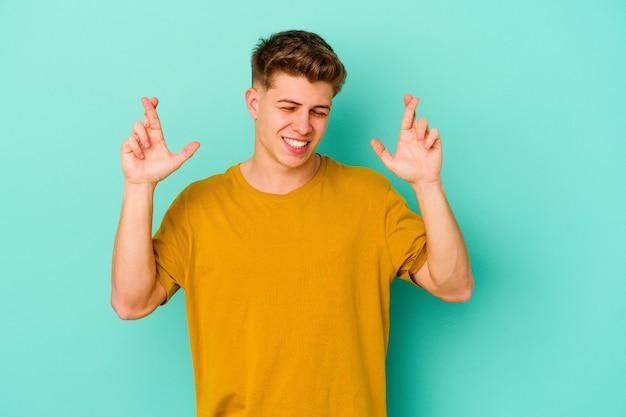 행운을 갖는 파란색 배경 횡단 손가락에 고립 된 젊은 백인 남자
