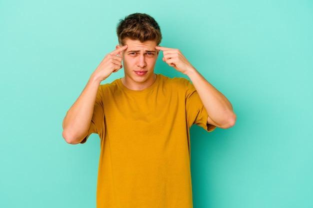 Молодой кавказский человек, изолированные на синем фоне, сосредоточился на задаче, держа указательные пальцы, указывая головой.
