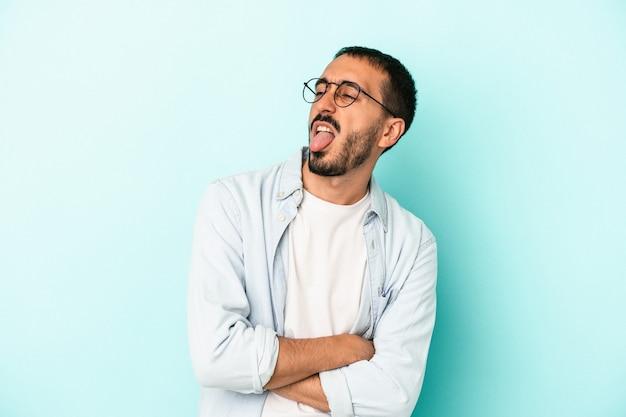 青の背景に孤立した若い白人男性は、面白いとフレンドリーな舌を突き出しています。