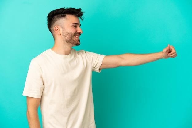 Молодой кавказский человек изолирован на синем фоне, показывая жест рукой вверх
