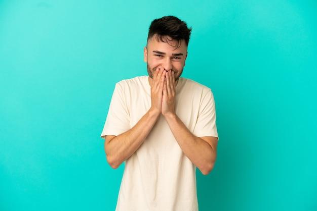 Молодой кавказский человек, изолированные на синем фоне, счастливый и улыбающийся, прикрывая рот руками