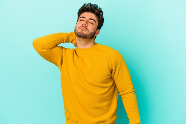 Молодой кавказский человек изолирован на синем фоне с болью в шее из-за стресса, массируя и касаясь ее рукой.