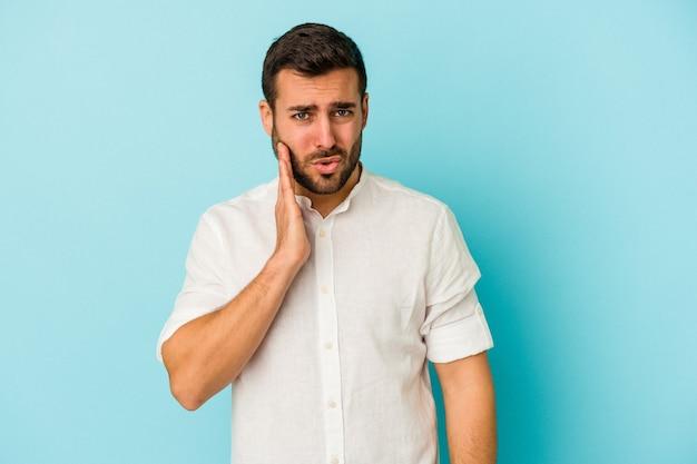 強い歯の痛み、臼歯の痛みを持っている青い背景に分離された若い白人男性。