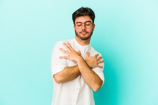 파란색 배경에 고립 된 젊은 백인 남자 포옹, 평온하고 행복 하 게 웃 고.