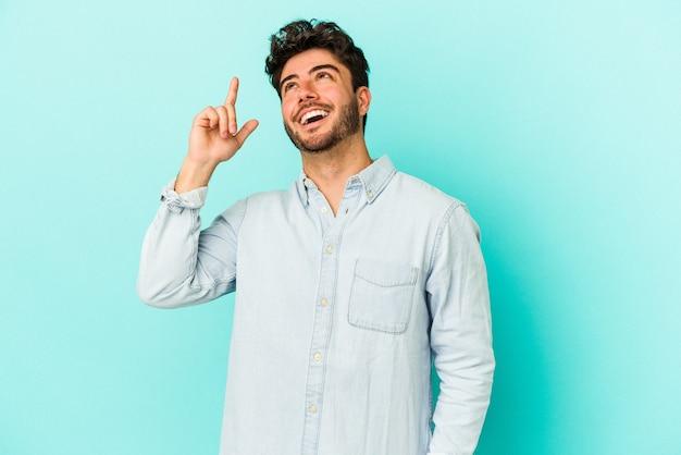 파란색 배경에 고립 된 젊은 백인 남자는 빈 공간을 보여주는 두 앞 손가락으로 나타냅니다.
