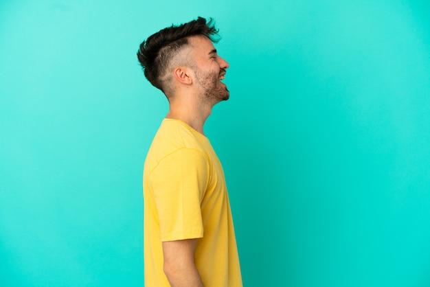 Молодой человек кавказской изолирован на синем фоне, смеясь в боковом положении