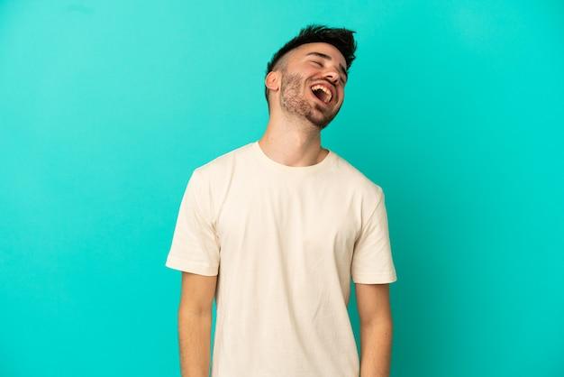 Молодой кавказский человек, изолированные на синем фоне смеясь