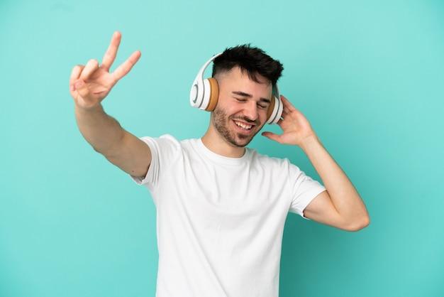 Молодой кавказский человек изолирован на синем фоне, слушает музыку и поет