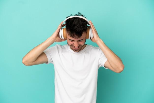 Молодой человек кавказской изолирован на синем фоне, слушая музыку
