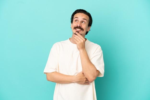 笑顔で見上げる青い背景に分離された若い白人男性