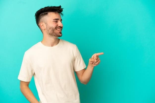 Молодой кавказский человек изолирован на синем фоне, указывая пальцем в сторону и представляет продукт