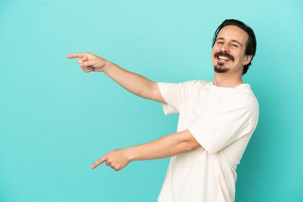横に指を指し、製品を提示する青い背景に分離された若い白人男性