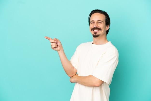 横に指を指している青い背景に分離された若い白人男性