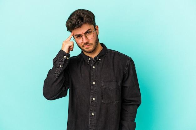 Молодой человек кавказской изолирован на синем фоне указывая храм пальцем, думая, сосредоточился на задаче.