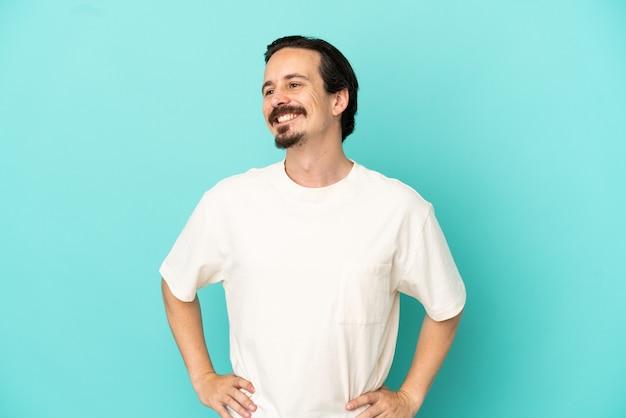 腰に腕と笑顔でポーズをとって青い背景で隔離の若い白人男性