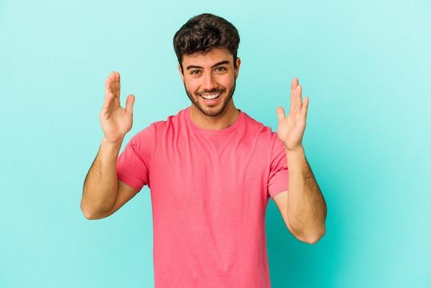 즐거운 놀라움을 받고, 흥분하고 손을 올리는 파란색 배경에 고립 된 젊은 백인 남자.