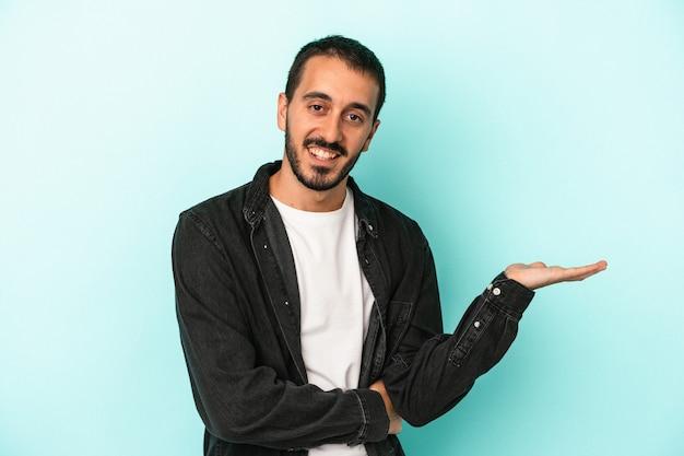 手のひらにコピースペースを示し、腰に別の手を保持している青い背景で隔離の若い白人男性。
