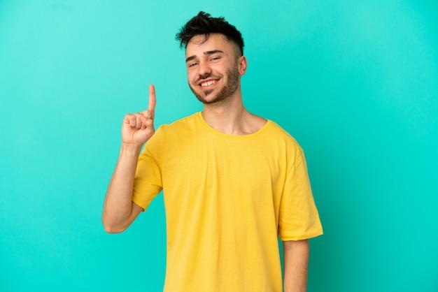 最高の兆候を示して指を持ち上げて青い背景で隔離の若い白人男性