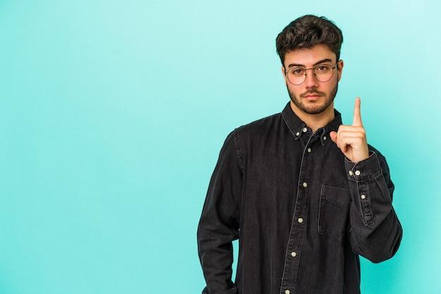 指で 1 番を示す青色の背景に分離された若い白人男性。