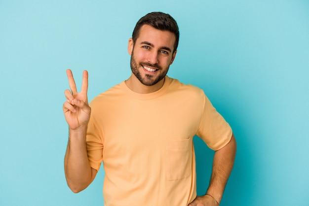 손가락으로 2 번을 보여주는 파란색 배경에 고립 된 젊은 백인 남자.