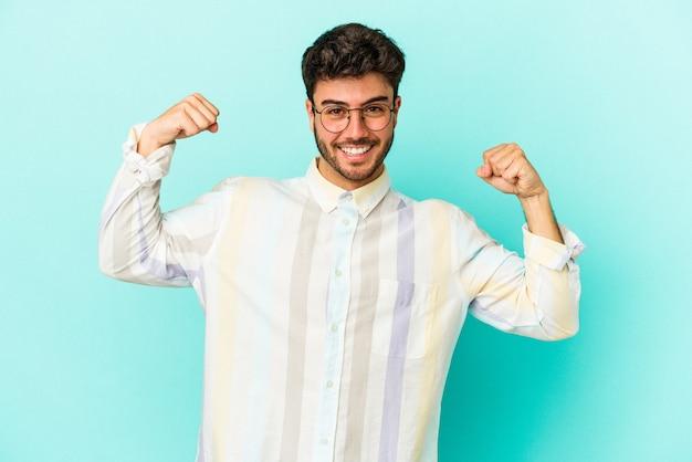 팔, 여성 힘의 상징으로 힘 제스처를 보여주는 파란색 배경에 고립 된 젊은 백인 남자