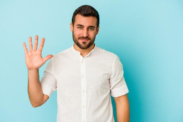Молодой кавказский человек, изолированных на синем фоне, улыбается веселый, показывая номер пять с пальцами.