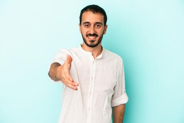 挨拶のジェスチャーでカメラに手を伸ばして青い背景で隔離の若い白人男性。
