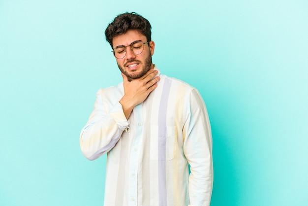 파란색 배경에 고립 된 젊은 백인 남자는 바이러스 또는 감염으로 인해 목에 통증을 앓고 있습니다.