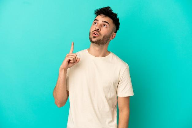 Молодой кавказский человек изолирован на синем фоне, думая об идее, указывая пальцем вверх