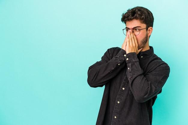 Молодой кавказский человек, изолированные на синем фоне, задумчивый глядя на копию пространства, охватывающего рот рукой.