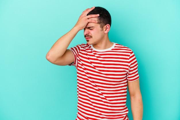 Молодой человек кавказской изолирован на синем фоне трогательно виски и имеет головную боль.