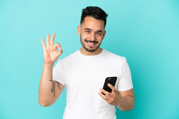 Молодой кавказский человек изолирован на синем фоне с помощью мобильного телефона и делает знак ок