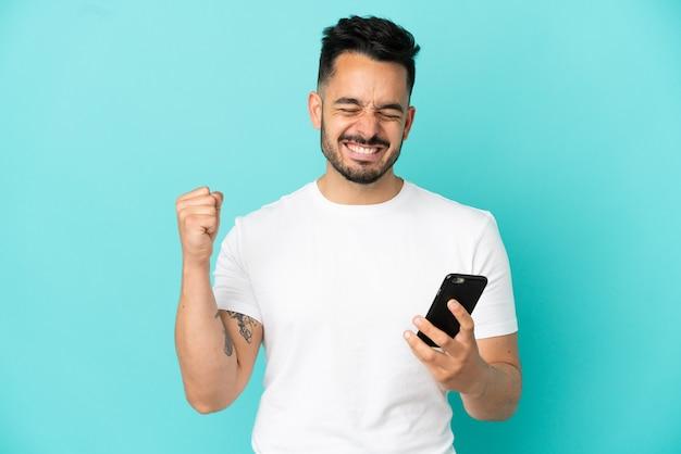 Молодой кавказский человек изолирован на синем фоне с помощью мобильного телефона и делает жест победы