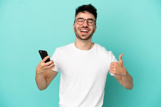 Молодой человек кавказской изолирован на синем фоне, используя мобильный телефон, делая большие пальцы руки вверх